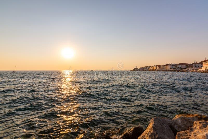 Puesta del sol hermosa sobre la ciudad de Piran, Eslovenia Luz mágica del sol sobre la luz suave del mar adriático y de la costa  fotografía de archivo libre de regalías