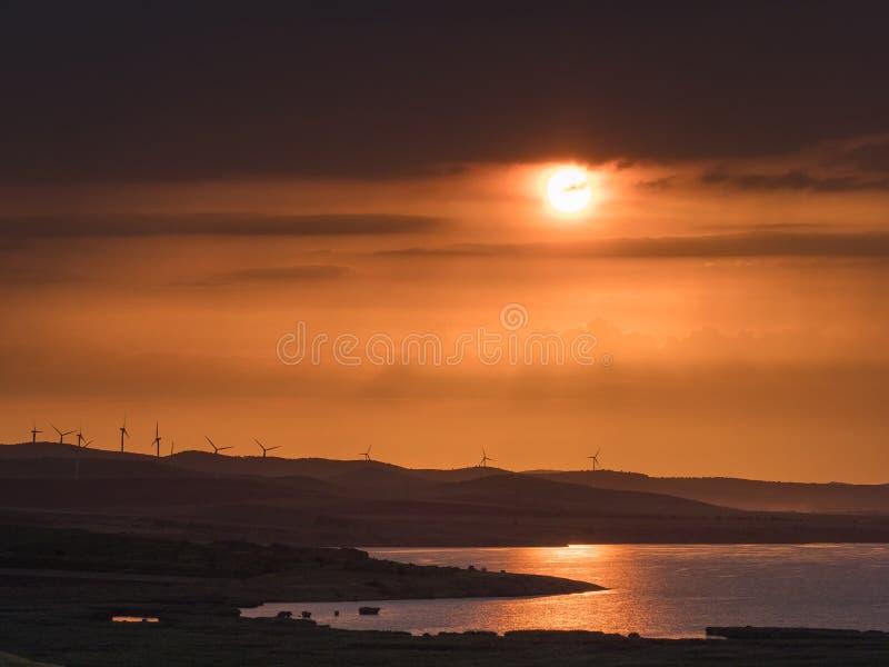Puesta del sol hermosa sobre las colinas y el agua y las siluetas de las turbinas de viento en el horizonte imagen de archivo libre de regalías