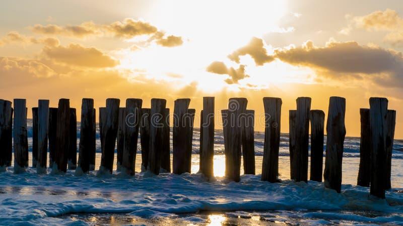 Puesta del sol hermosa sobre rompeolas en Zelanda fotos de archivo