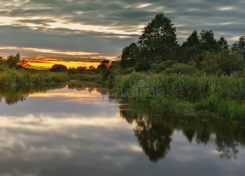 Puesta del sol hermosa sobre un río tranquilo imagen de archivo