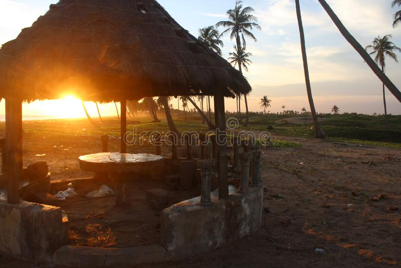 puesta del sol hermosa a través de una choza de la playa foto de archivo libre de regalías