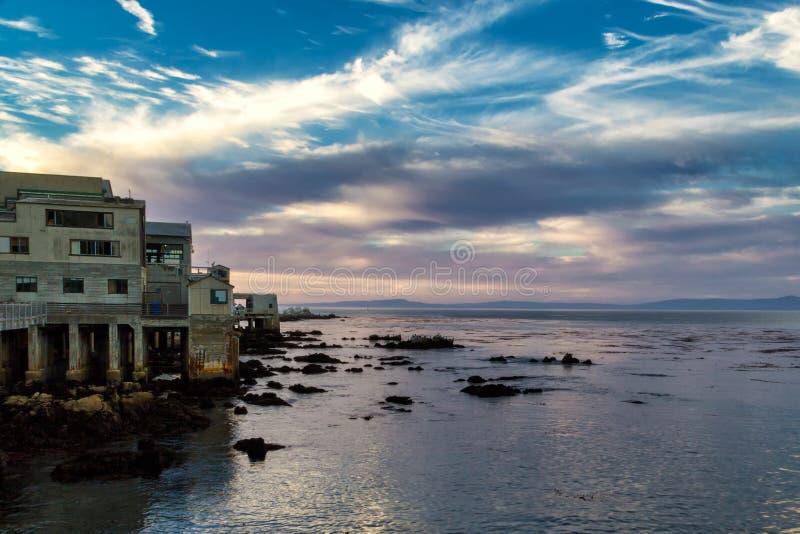 Puesta del sol hermosa y edificios costeros viejos en Monterey, California foto de archivo libre de regalías