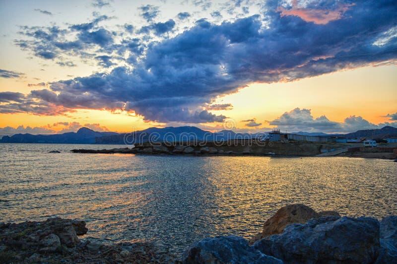 Puesta del sol hermosa y nubes del verano sobre el mar y las montañas Viajes fotografía de archivo libre de regalías