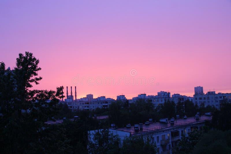 puesta del sol imponente, zonas urbanas, sombras del árbol, chimeneas de la fábrica y siluetas de edificios residenciales de gran foto de archivo