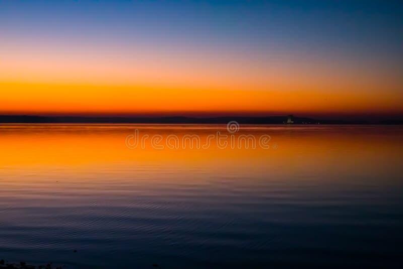 Puesta del sol increíble, brillante sobre el agua imagenes de archivo