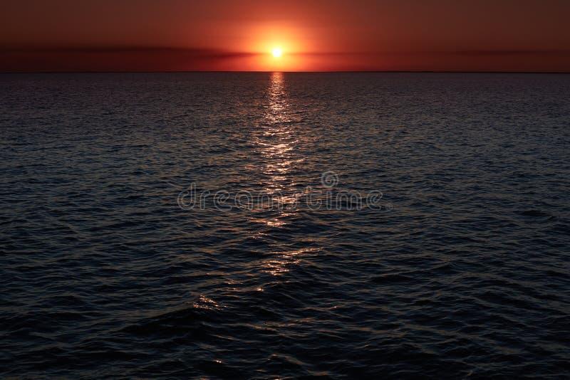 Puesta del sol increíblemente hermosa sobre el mar con las ondas Paisajes hermosos Puesta del sol del mar del oro Paisaje ardient foto de archivo