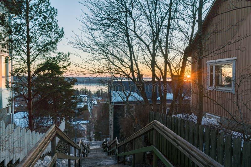 Puesta del sol del invierno sobre el lago y las calles septentrionales pintorescas en Finlandia foto de archivo