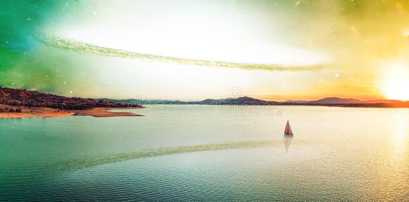 Puesta del sol irreal escénica sobre el lago hermoso y el velero solo en el planeta extranjero Elementos de esta imagen equipados fotografía de archivo libre de regalías