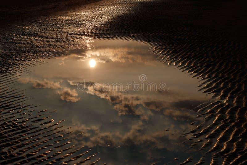 Puesta del sol ligera de oro que refleja en superficie del agua imagenes de archivo