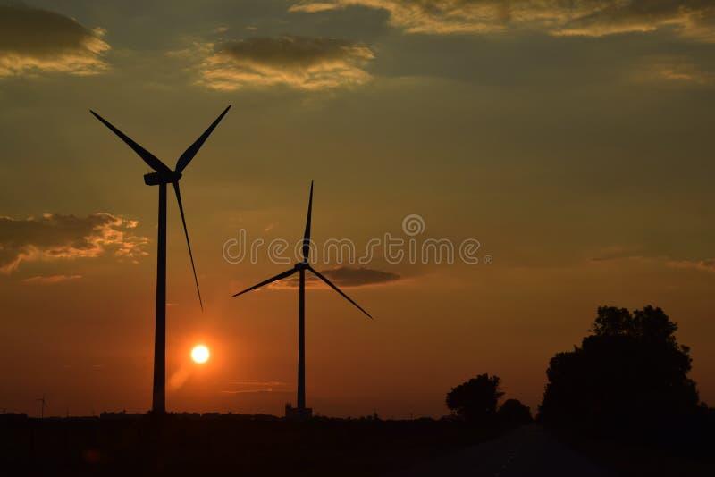 Puesta del sol mágica detrás de los generadores de un viento imagen de archivo libre de regalías