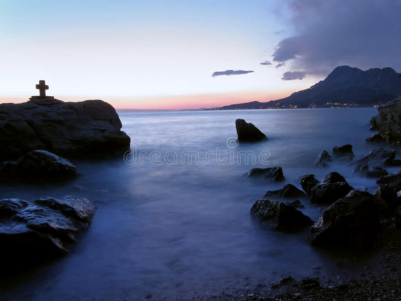 Puesta del sol mágica en el mar con la silueta cruzada imagen de archivo