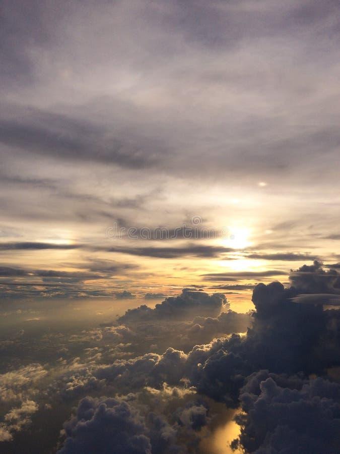 Puesta del sol mágica sobre las nubes de tormenta de la ventana del aircarft imagen de archivo