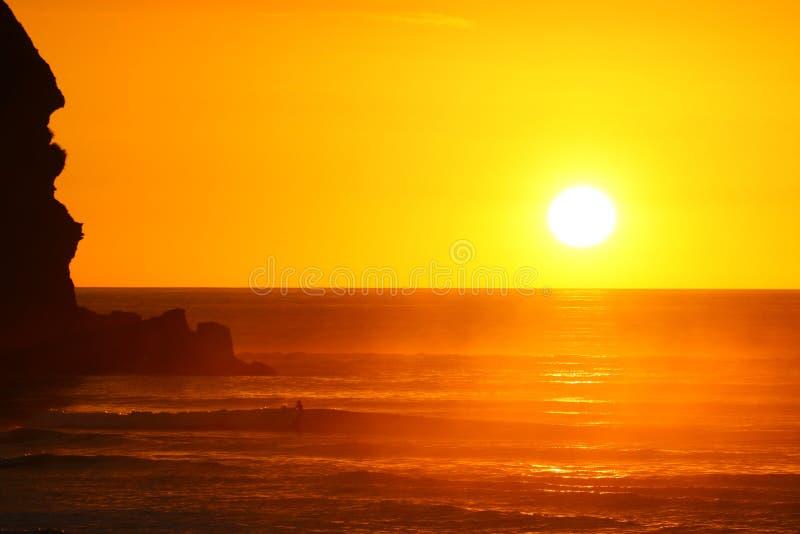 Puesta del sol magnífica en la playa de Piha foto de archivo