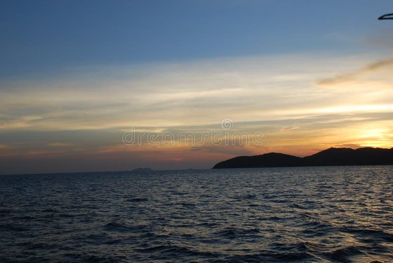 Puesta del sol maravillosa sobre las montañas por el mar imagen de archivo libre de regalías