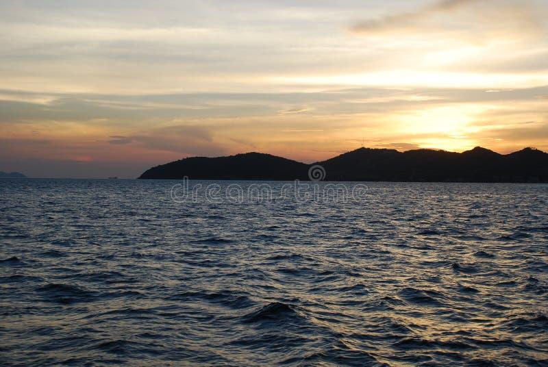 Puesta del sol maravillosa sobre las montañas por el mar foto de archivo