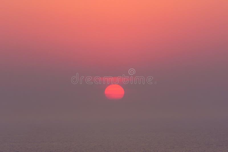 Puesta del sol nebulosa en el mar con el sol rojo fotografía de archivo libre de regalías