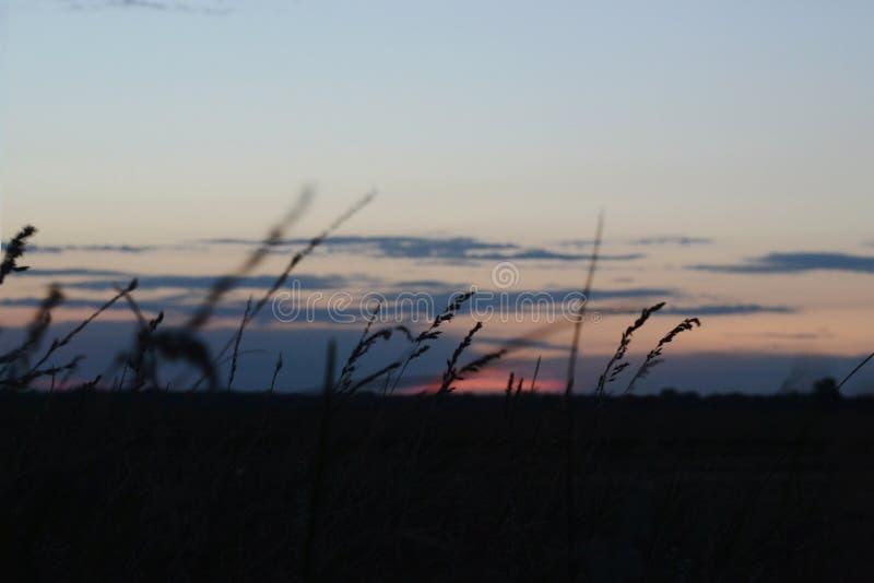 Puesta del sol nublada en el pueblo fotografía de archivo libre de regalías