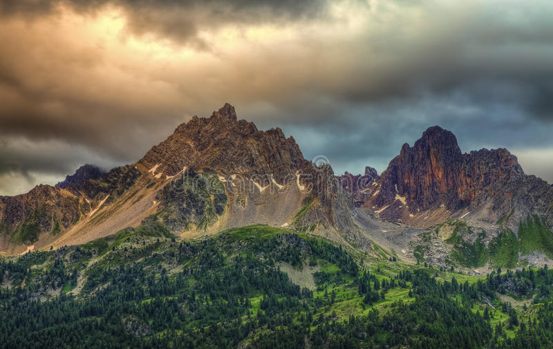 Puesta del sol nublada sobre los picos foto de archivo libre de regalías