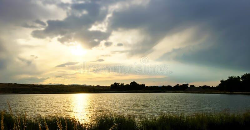 Puesta del sol nublada sobre un lago imagen de archivo