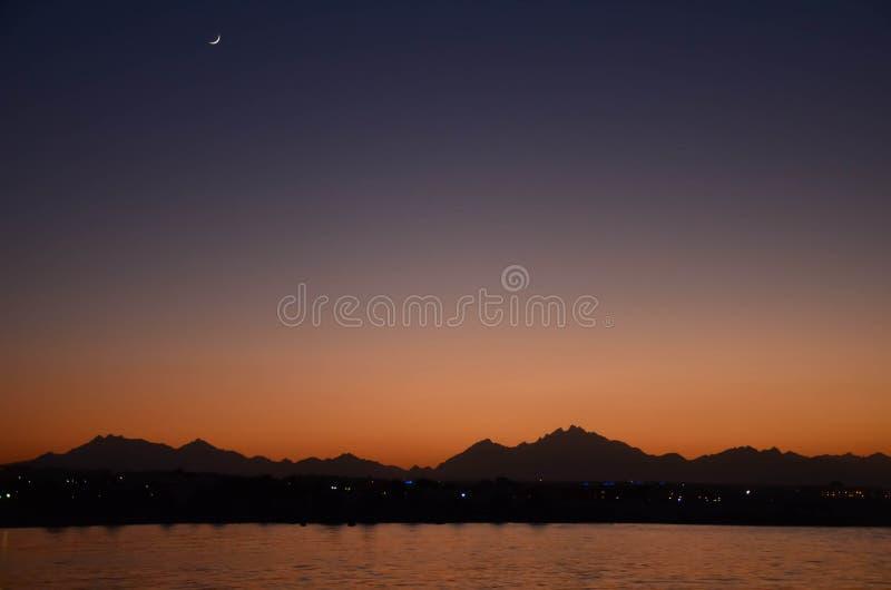 Puesta del sol oriental hermosa: sol y luna foto de archivo