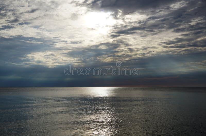 Puesta del sol oscura Los rayos del sol brillan sobre la superficie del lago fotografía de archivo libre de regalías
