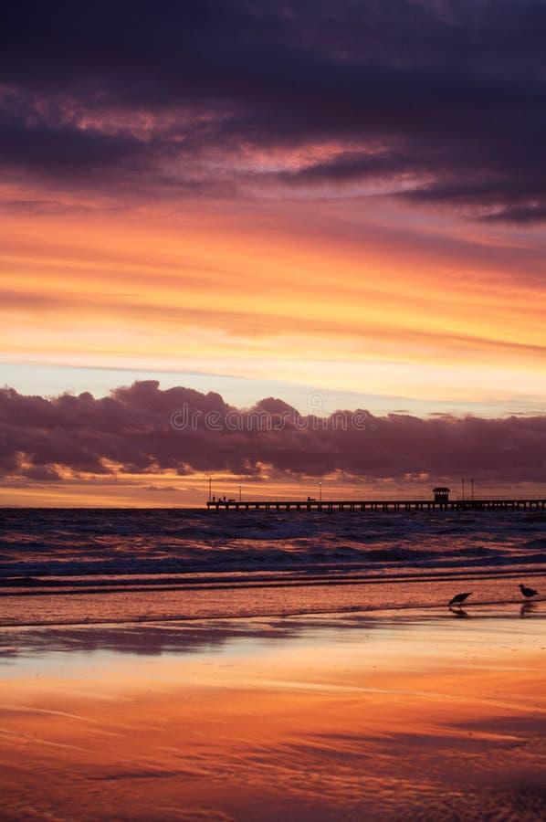 Puesta del sol púrpura y anaranjada sobre el mar fotos de archivo