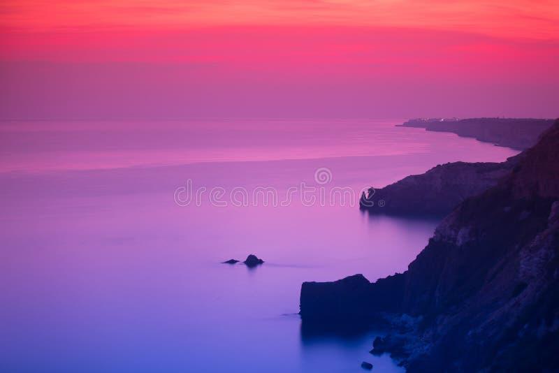 Puesta del sol púrpura y rosada sobre el océano fotos de archivo