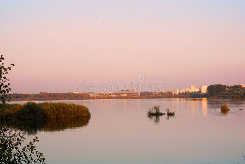 Puesta del sol del paisaje con la ciudad y el lago europeos Paisaje del otoño con los árboles amarillos y verdes, río fotos de archivo
