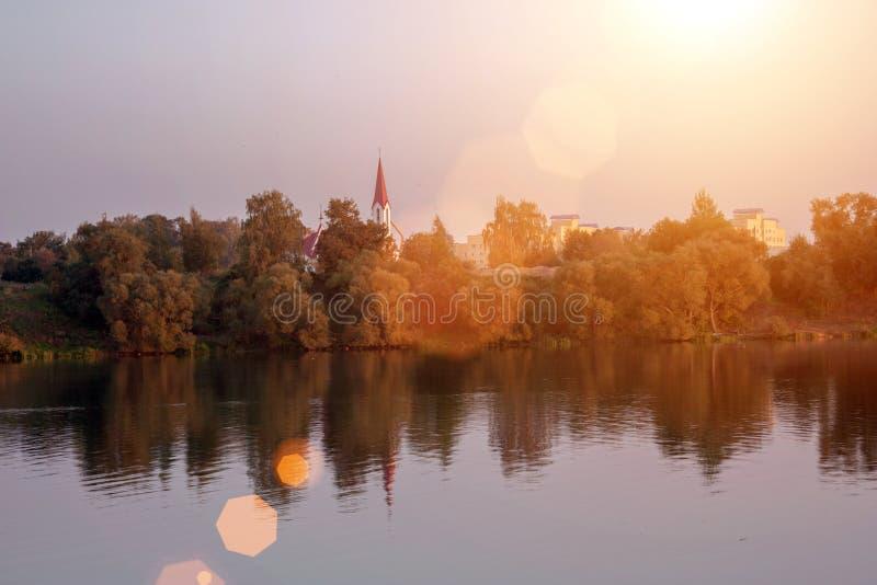 Puesta del sol del paisaje con la ciudad y el lago europeos Paisaje del otoño con los árboles y el río amarillos y verdes imagen de archivo libre de regalías