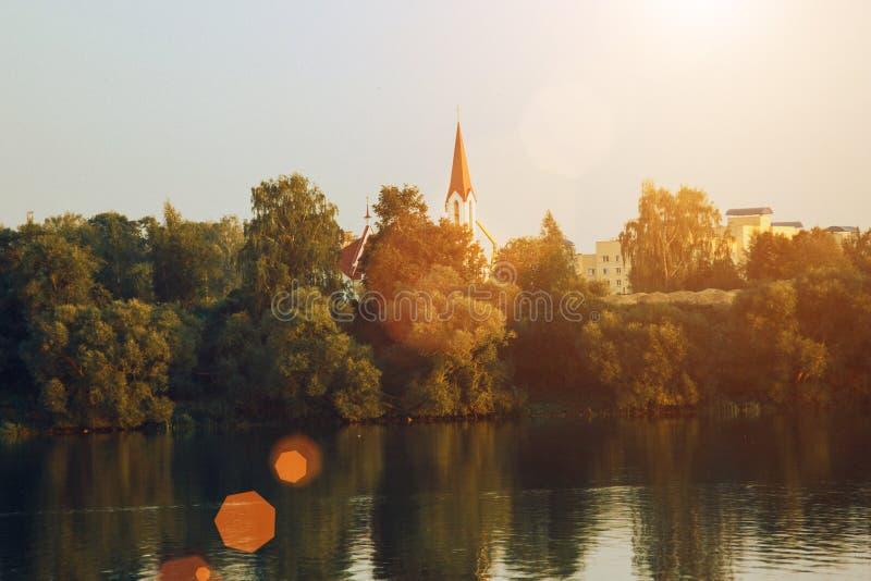 Puesta del sol del paisaje con la ciudad y el lago europeos Paisaje del otoño con los árboles y el río amarillos y verdes imágenes de archivo libres de regalías