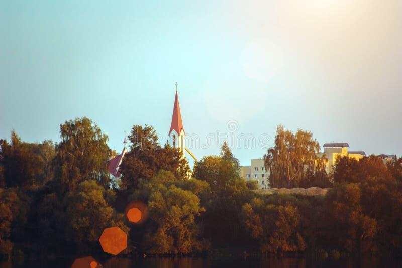 Puesta del sol del paisaje con la ciudad y el lago europeos Paisaje del otoño con los árboles y el río amarillos y verdes imagenes de archivo