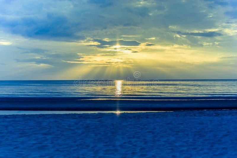 Puesta del sol del paisaje en la playa con la llamarada ligera en el océano en color de proceso cruzado imagen de archivo