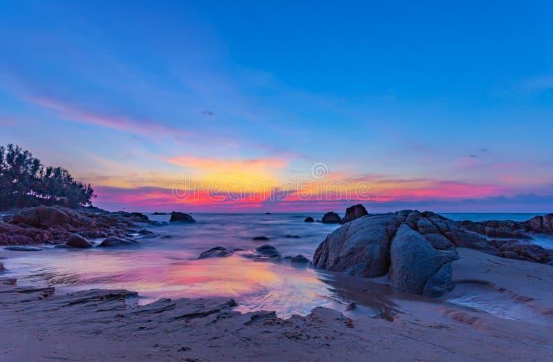 puesta del sol del paisaje en la roca en la playa de Pilay Natai imagen de archivo