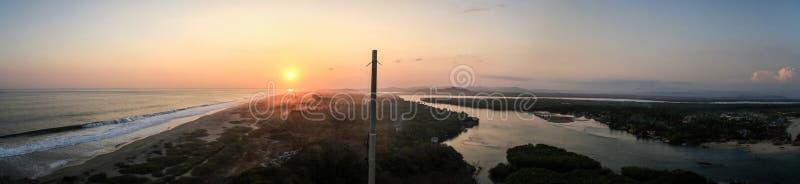 Puesta del sol panorámica en el Océano Pacífico en un lado y el Lagunas de Chacahua en el otro, Chacahua, Oaxaca, México fotos de archivo