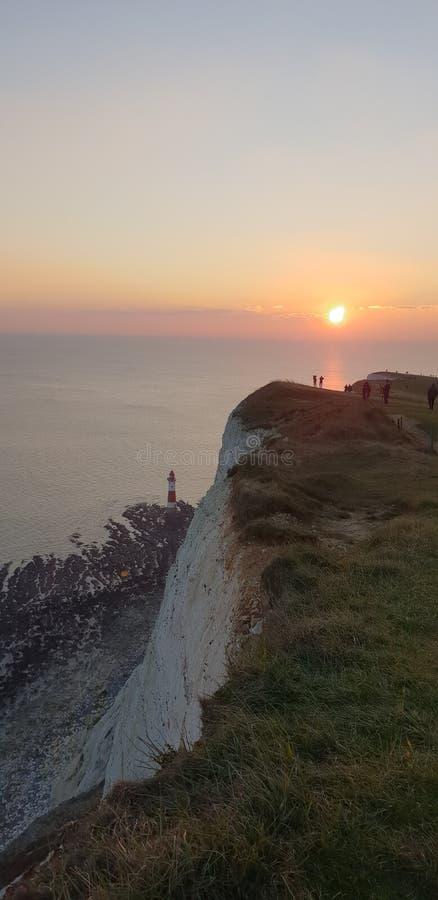Puesta del sol principal con playas de Eastbourne Sussex del faro imágenes de archivo libres de regalías