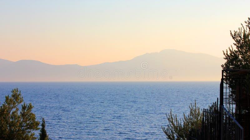 Puesta del sol que pasa por alto el mar y las montañas imagenes de archivo