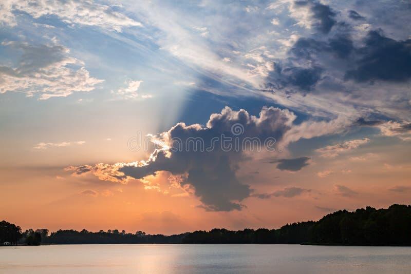 Puesta del sol que sorprende en el lago con los rayos del sol en nubes imagen de archivo