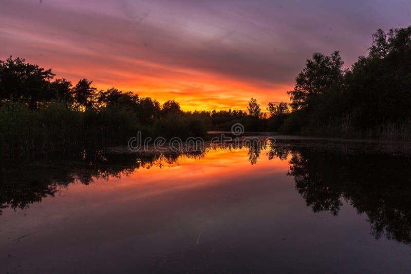 Puesta del sol que sorprende sobre una charca con reflexiones en el agua cerca de Waterschei en B?lgica fotos de archivo