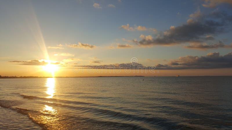 Puesta del sol reflectora en el océano con la marea que viene adentro imagen de archivo
