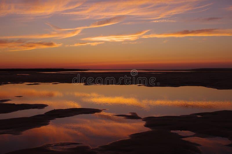 Puesta del sol reflejada sobre piscinas de marea imagen de archivo libre de regalías