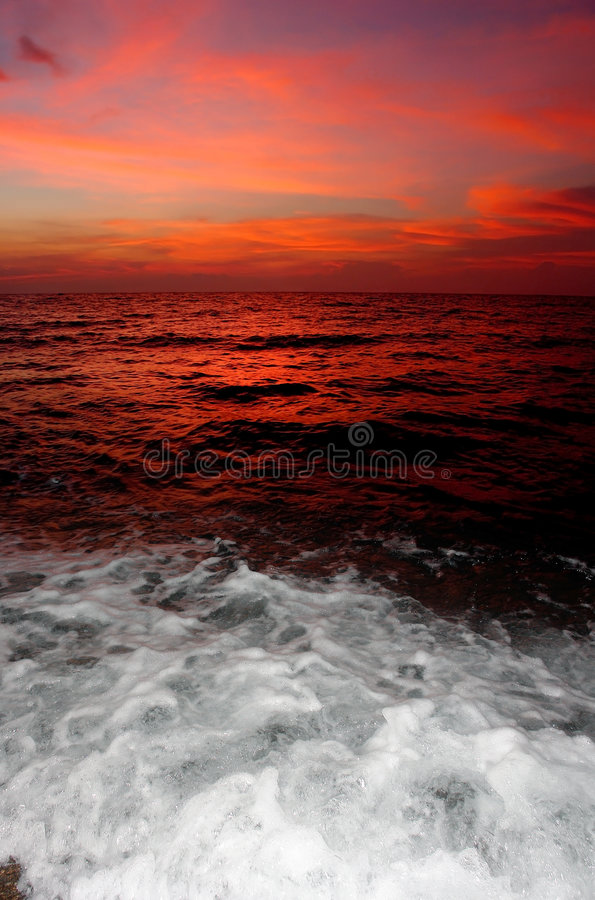 Puesta del sol roja con la fractura del agua. fotografía de archivo libre de regalías