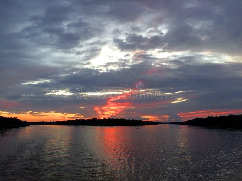 Puesta del sol roja hermosa en el río Amazonas: Brasil fotos de archivo