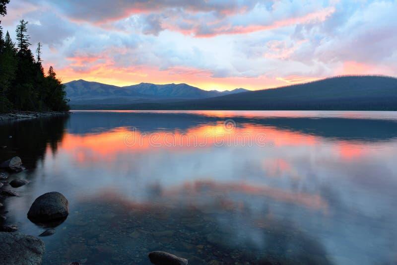 Puesta del sol roja hermosa en las montañas y el lago McDonald en Parque Nacional Glacier imagen de archivo
