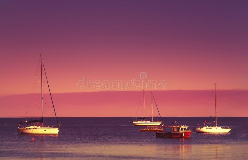 Puesta del sol roja sobre el mar azul, el cielo púrpura y los yates en el estacionamiento Paisaje escénico del mar del verano por imagen de archivo