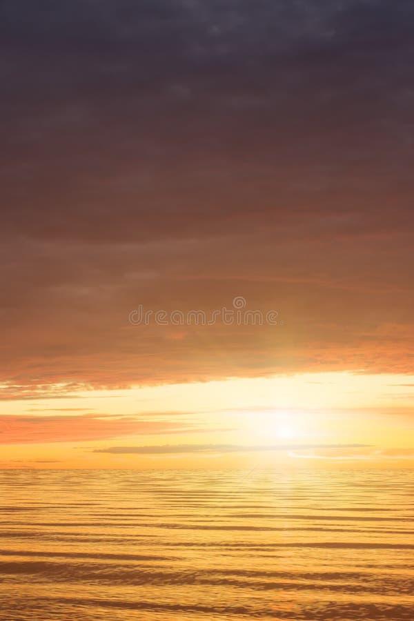 Puesta del sol roja sobre el mar, rico en las nubes oscuras, rayos de la luz E foto de archivo libre de regalías