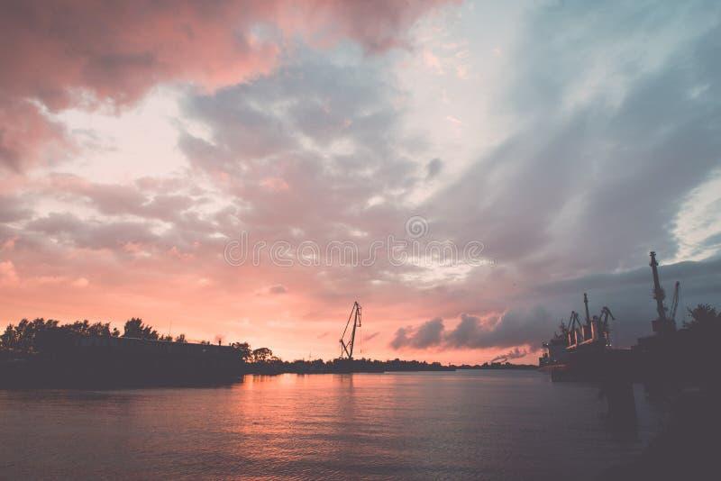 puesta del sol rojiza sobre puerto - efecto retro del vintage imagen de archivo libre de regalías