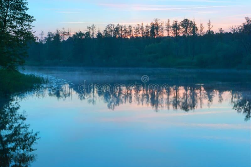 puesta del sol Rojo-amarilla sobre el lago, salida del sol y niebla sobre el río, cielo rosado en el amanecer imagenes de archivo