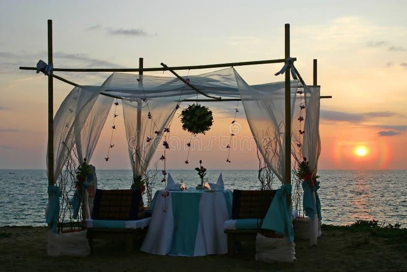 Puesta del sol romántica de la cena por el mar foto de archivo
