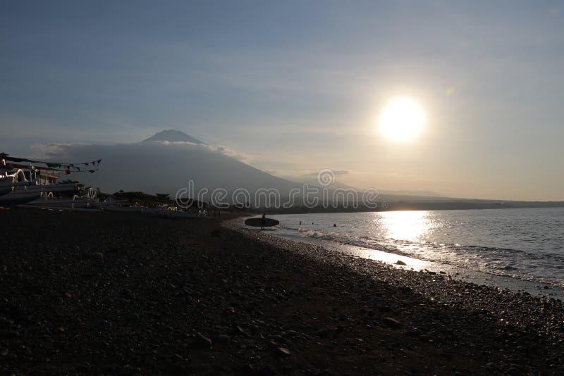 Puesta del sol romántica en la costa de mar en Indonesia La persona que practica surf va a gozar de paddleboard en la puesta del  imagen de archivo libre de regalías