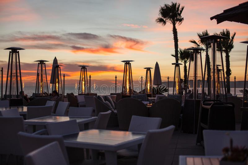 Puesta del sol romántica hermosa en el café de la playa con los calentadores al aire libre del patio imagen de archivo